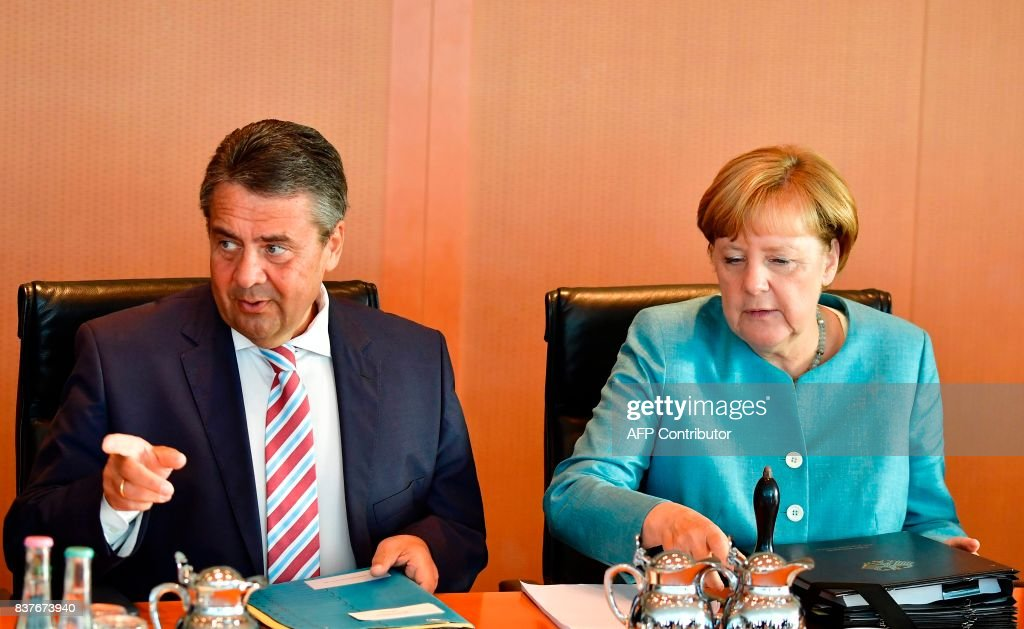 German Chancellor Angela Merkel (R) and German Vice Chancellor and German Foreign Minister Sigmar Gabriel await the start of the weekly cabinet meeting in Berlin, on August 23, 2017. /