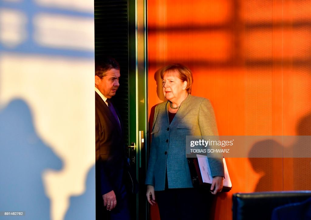 German Chancellor Angela Merkel and German Vice Chancellor and Foreign Minister Sigmar Gabriel confer at the beginning of the weekly cabinet meeting in Berlin on December 13, 2017. /