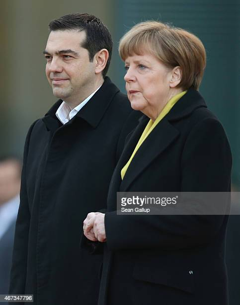 German Chancellor Angela Merkel and Greek Prime Minister Alexis Tsipras listen to their countries' national anthems upon his arrival for talks at the...