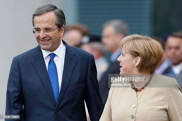 German Chancellor Angela Merkel and Greek Prime Minister Antonis Samaras review a guard of honour upon Samaras arrival at the Chancellery on August...