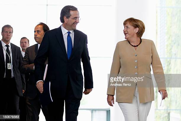 German Chancellor Angela Merkel and Greek Prime Minister Antonis Samaras arrive for a press statement at the Chancellery on August 24 2012 in Berlin...