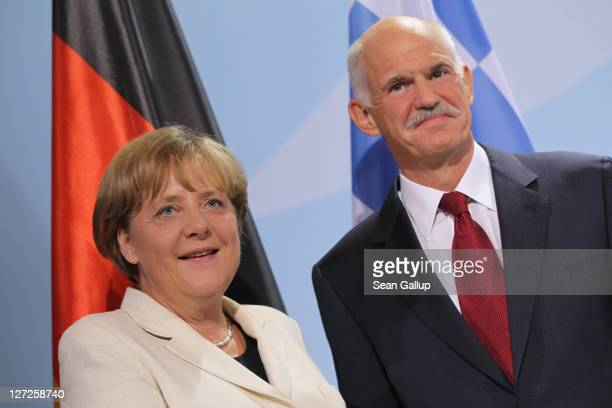 German Chancellor Angela Merkel and Greek Prime Minister George Papandreou depart after speaking to the media prior to talks at the Chancellery on...