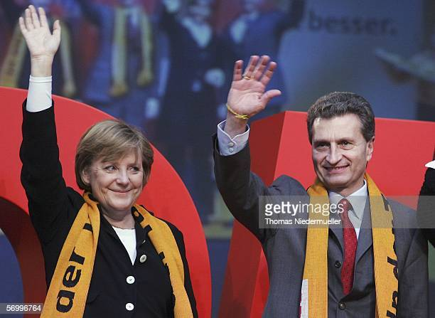 German Chancellor Angela Merkel and Guenther H Oettinger governor of the German state of BadenWuerttemberg wave to the audience during the CDU...
