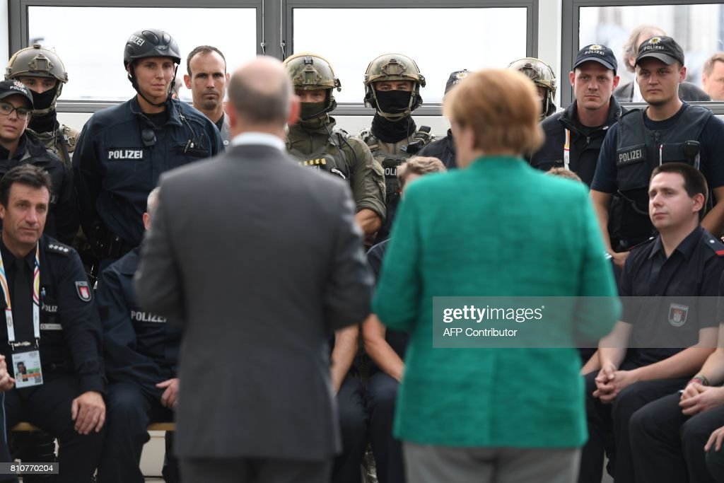 German Chancellor Angela Merkel (R) and Hamburg's mayor Olaf Scholz (L) talk with policemen and firemen who were deployed during the G20 summit in Hamburg, northern Germany, on July 8, 2017. / AFP PHOTO / Patrik STOLLARZ