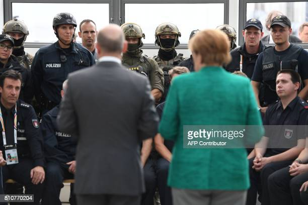 German Chancellor Angela Merkel and Hamburg's mayor Olaf Scholz talk with policemen and firemen who were deployed during the G20 summit in Hamburg...