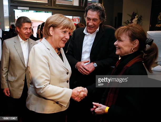 German Chancellor Angela Merkel and her husband Joachim Sauer are welcomed by German actors Angelica Domroese and Winfried Glatzeder for the...