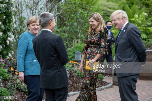 German Chancellor Angela Merkel and her husband Joachim Sauer chat with British Prime Minister Boris Johnson and wife Carrie Johnson at a drinks...