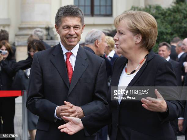 German Chancellor Angela Merkel and her husband Joachim Sauer gesture on their arrival for a ceremony to celebrate the 60th anniversary of the...