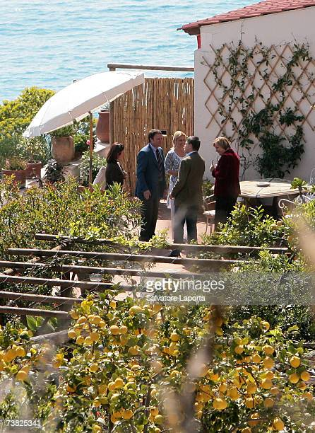 German Chancellor Angela Merkel and her husband Joachim Sauer speak with Linda Mattera from Hotel Miramare Italy on arriving at a villa by the sea in...