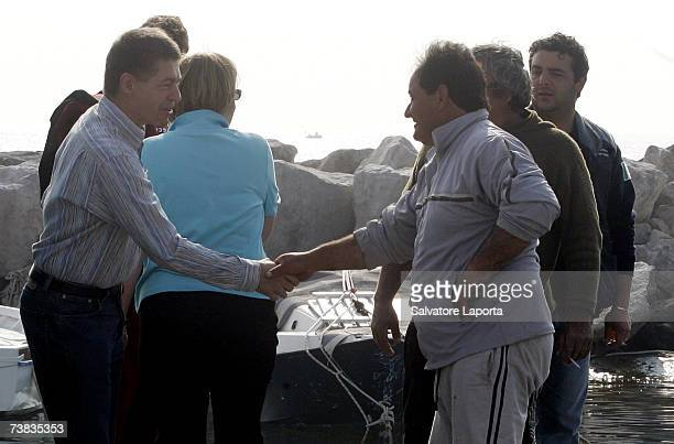German Chancellor Angela Merkel and her husband Joachim Sauer talk to a fisherman with a fresh catch of fish in the coastal town of Sant'Angelo...