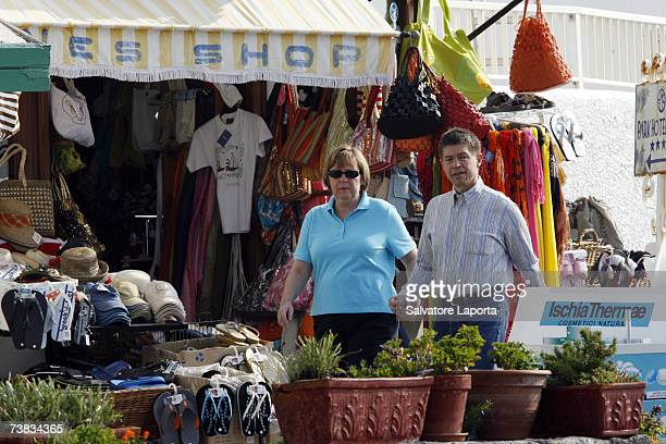 German Chancellor Angela Merkel and her husband Joachim Sauer walk past a market stall in a street in the town of Sant'Angelo d'Ischia on the Island...