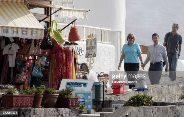 German Chancellor Angela Merkel and her husband Joachim Sauer walk by a market stall in the coastal town of Sant'Angelo d'Ischia on the Island of...