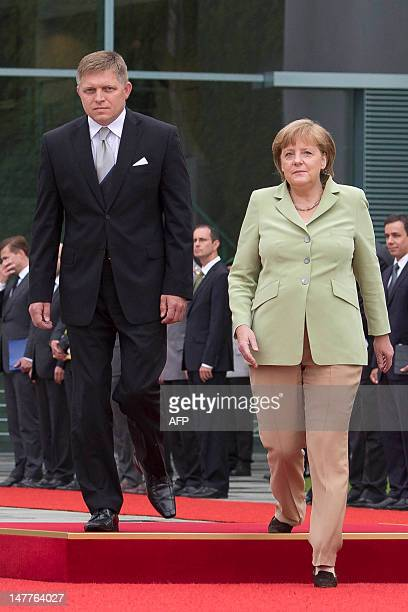 German Chancellor Angela Merkel and her Slovak counterpart Robert Fico review a guard of honour at the Chancellery in Berlin on July 03, 2012. AFP...