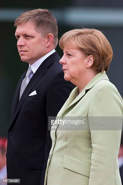 German Chancellor Angela Merkel and her Slovak counterpart Robert Fico review a guard of honour before a meeting at the Chancellory in Berlin on July...
