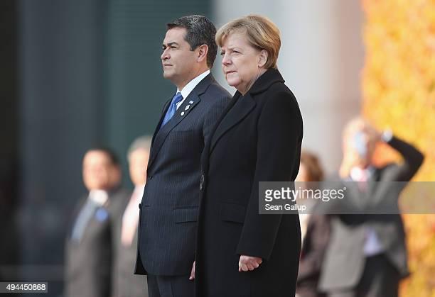 German Chancellor Angela Merkel and Honduran President Juan Orlando Hernandez listen to their countries' respective national anthems upon Hernandez's...