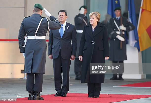 German Chancellor Angela Merkel and Honduran President Juan Orlando Hernandez finish reviewing a guard of honour upon Hernandez's arrival for an...