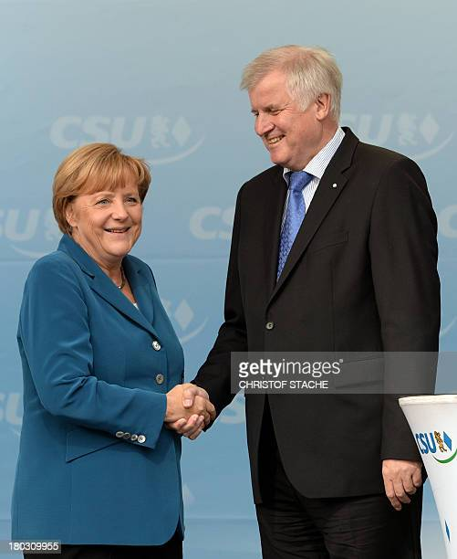 German Chancellor Angela Merkel and Horst Seehofer Bavarian State Premier shake hands during an election campaign event of the German Christian...