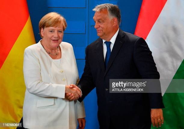 German Chancellor Angela Merkel and Hungarian Prime Minister Viktor Orban shake hands following a press conference during their meeting in the...