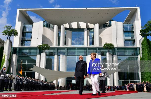 German Chancellor Angela Merkel and Indian Prime Minister Narendra Modi inspect a military honor guard prior to talks at the Chancellery in Berlin on...