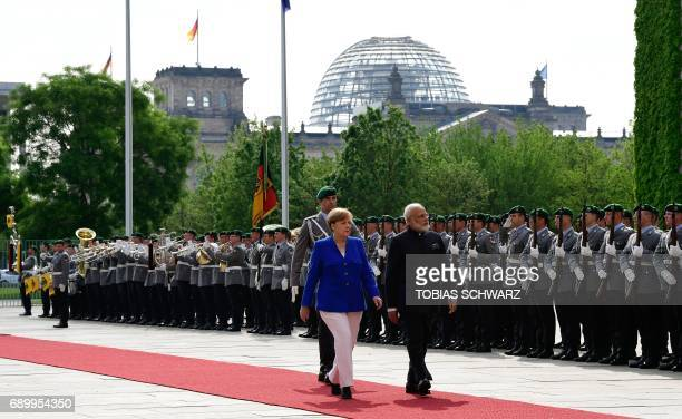 German Chancellor Angela Merkel and Indian Prime Minister Narendra Modi inspect a military honor guard prior to talks at the Chancellery in Berlin,...