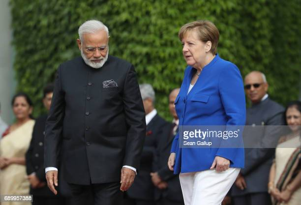 German Chancellor Angela Merkel and Indian Prime Minister Narendra Modi arrive to review a guard of honour prior to consultations between the German...