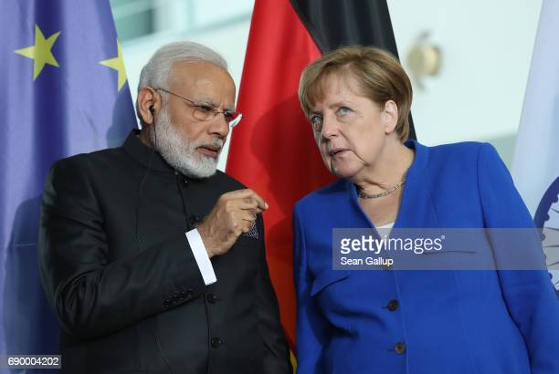 German Chancellor Angela Merkel and Indian Prime Minister Narendra Modi chat during a signing ceremony of contracts between the German and Indian...