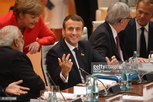German Chancellor Angela Merkel and Indian Prime Minister Narendra Modi listen to French President Emmanuel Macron during the plenary session at the...