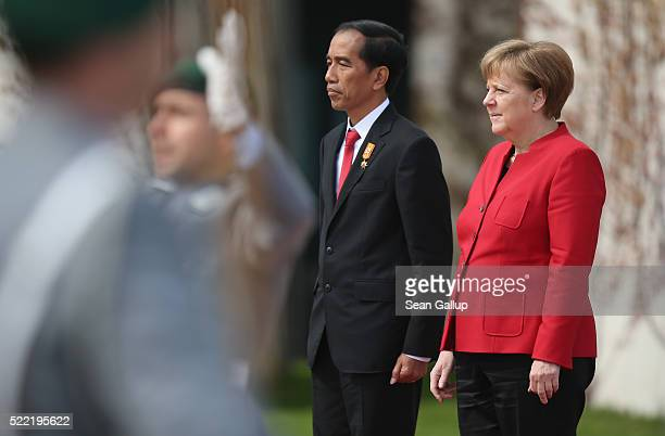 German Chancellor Angela Merkel and Indonesian President Joko Widodo listen to a military band perform their nations' respect anthems upon his...