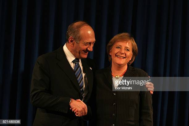 German Chancellor Angela Merkel and interim Israeli Prime Minister Ehud Olmert smile after a joint news conference in Jerusalem Sunday January 29,...
