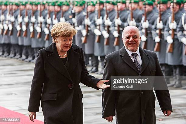 German Chancellor Angela Merkel and Iraqi Prime Minister Haider AlAbadi review a guard of honour upon AlAbadi's arrival at the Chancellery for talks...