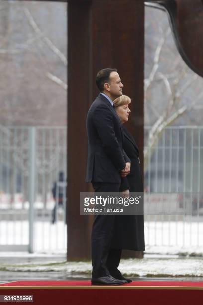German Chancellor Angela Merkel and Irish Prime Minister Leo Varadkar stand for their respective national anthems at the courtyard of the German...