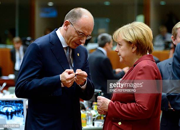 German Chancellor Angela Merkel and Italian Prime Minister Enrico Letta talk on October 24 2013 during a European Council meeting at the EU...