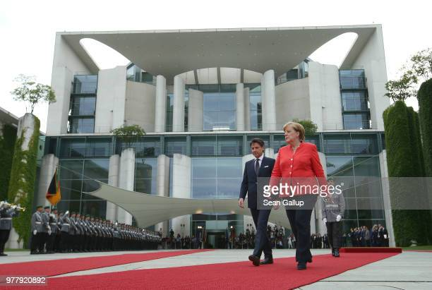 German Chancellor Angela Merkel and Italian Prime Minister Guiseppe Conte review a guard of honor upon Conte's arrival at the Chancellery on June 18...