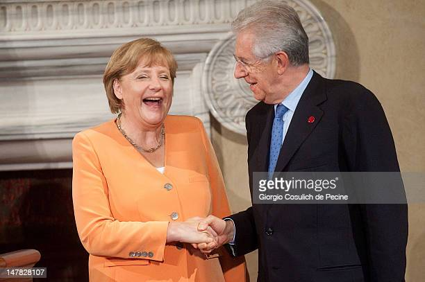 German chancellor Angela Merkel and Italian Prime Minister Mario Monti, shake hands at the end of press conference, after a bilateral meeting at...