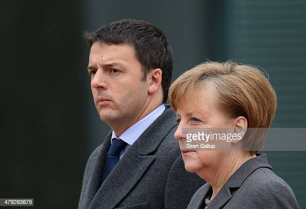 German Chancellor Angela Merkel and Italian Prime Minister Matteo Renzi listen to their countries' respective national anthems upon Rnezi's arrival...
