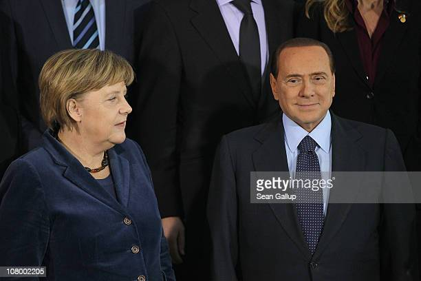 German Chancellor Angela Merkel and Italian Prime Minister Silvio Berlusconi arrive for a group photo of the two countries' delegations at the...