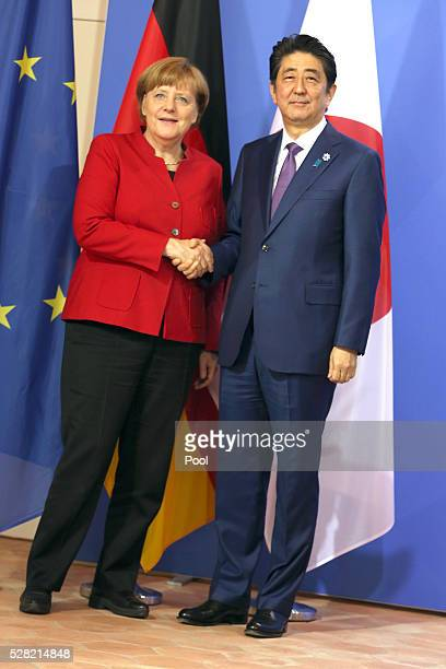 German Chancellor Angela Merkel and Japanese Prime Minister Shinzo Abe shake hands during a joint press conference following talks at Schloss...