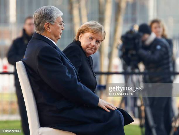 German Chancellor Angela Merkel and Kazakh President KassymJomart Tokayev sit as they listen to the national anthems during a welcoming ceremony on...