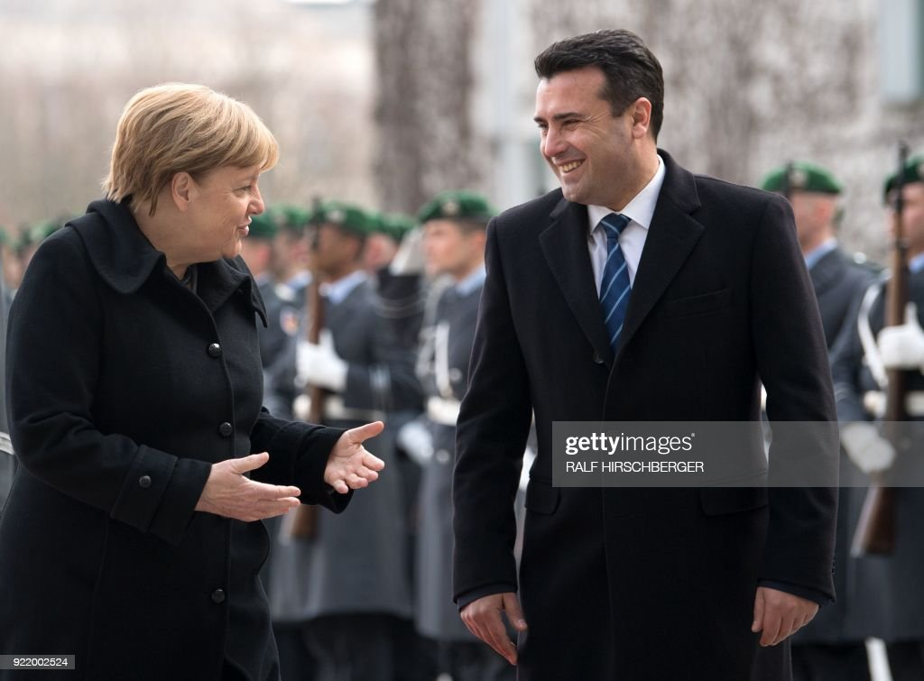 German Chancellor Angela Merkel and Macedonian Prime Minister Zoran Zaev review an honour guard in the courtyard of the Chancellery prior to their meeting on February 21, 2018 in Berlin. / AFP PHOTO / dpa / Ralf Hirschberger / Germany OUT