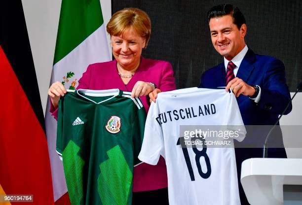 German Chancellor Angela Merkel and Mexican President Enrique Pena Nieto exchange the shirts of their national football teams before touring the...