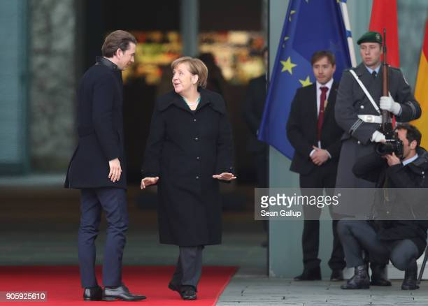 German Chancellor Angela Merkel and new Austrian Chancellor Sebastian Kurz chat upon Kurz's arrival at the Chancellery on January 17 2017 in Berlin...