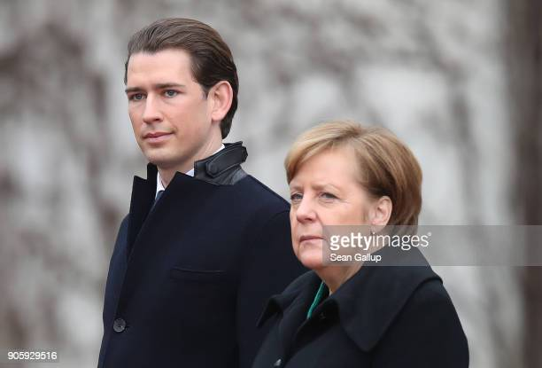 German Chancellor Angela Merkel and new Austrian Chancellor Sebastian Kurz listen to their countries' respective national anthems upon Kurz's arrival...