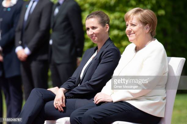 German Chancellor Angela Merkel and new Danish Prime Minister Mette Frederiksen sit side by side as the national anthems of the two countries are...