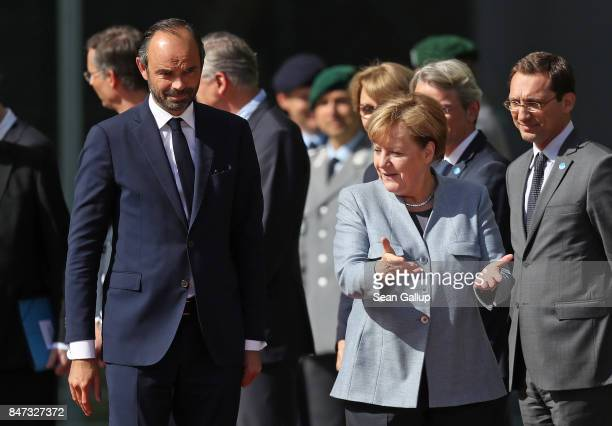 German Chancellor Angela Merkel and new French Prime Minister Edouard Philippe prepare to review a guard of honour upon Philippe's arrival at the...