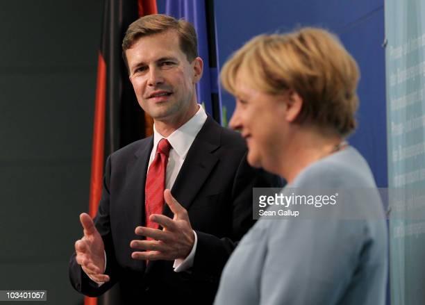 German Chancellor Angela Merkel and new German government spokesman Steffen Seibert speak at Seibert's official presentation as new spokesman at the...