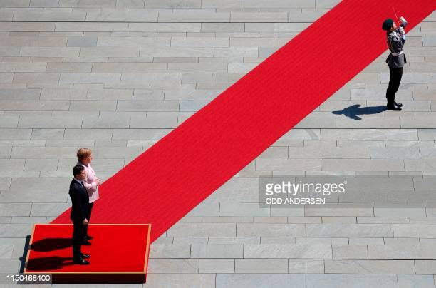 German Chancellor Angela Merkel and new Ukrainian President Volodymyr Zelensky inspect a military honor guard as he arrives for his first official...