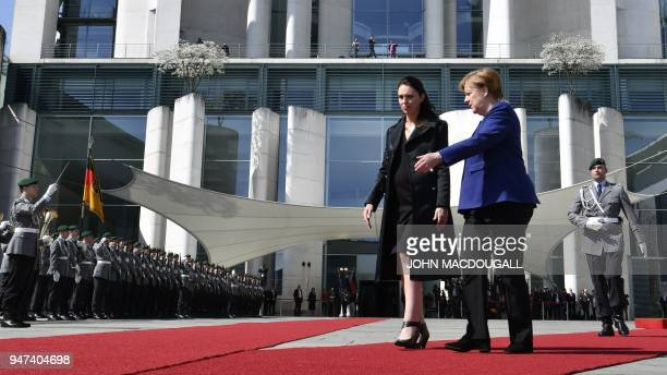 German Chancellor Angela Merkel and New Zealand's Prime Minister Jacinda Ardern walk on the red carpet during a welcoming ceremony with the military...