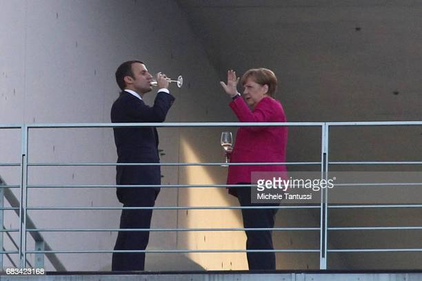 German Chancellor Angela Merkel and newlyelected French President Emmanuel Macron chat on the balcony of the Chancellery after their joint press...