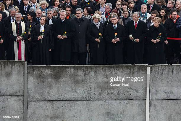 German Chancellor Angela Merkel and other dignitaries place flowers in between slats of the former Berlin Wall at the Berlin Wall Memorial at...