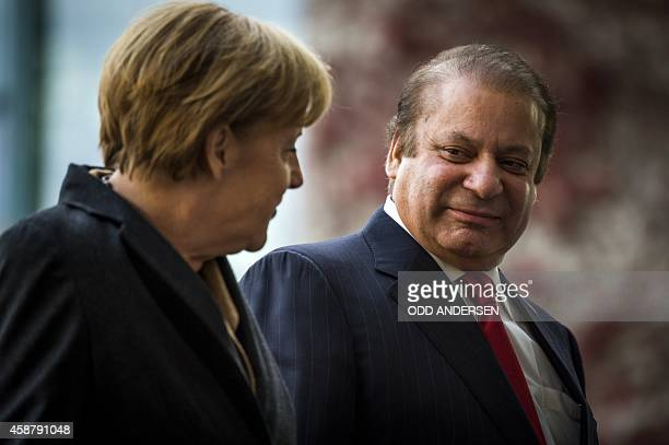 German Chancellor Angela Merkel and Pakistani Prime Minister Nawaz Sharif chat as they review a military guard of honour at a welcoming ceremony at...